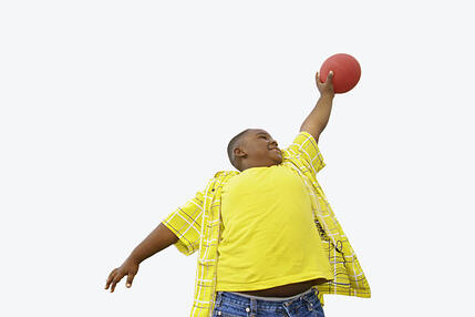 Boy holding ball in air