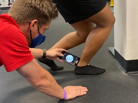 author measuring ankle dorsiflexion with smartphone