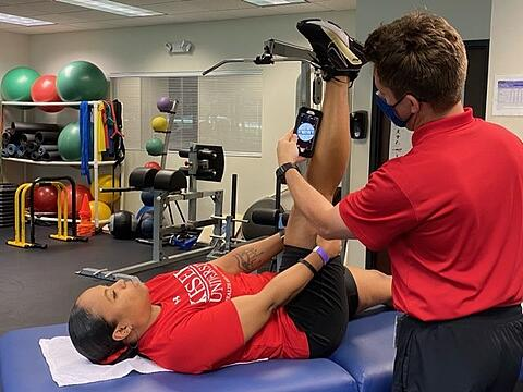 author measuring active knee extension with smartphone