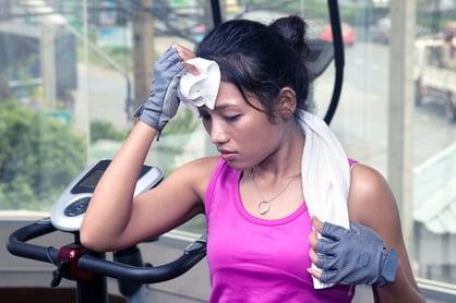 Woman wiping sweat off head
