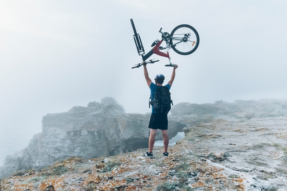 man on a mountain triumphantly holding a bike over his head
