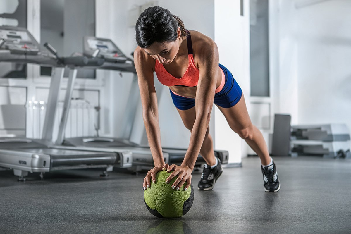 A woman doing a pushup with a medicine ball