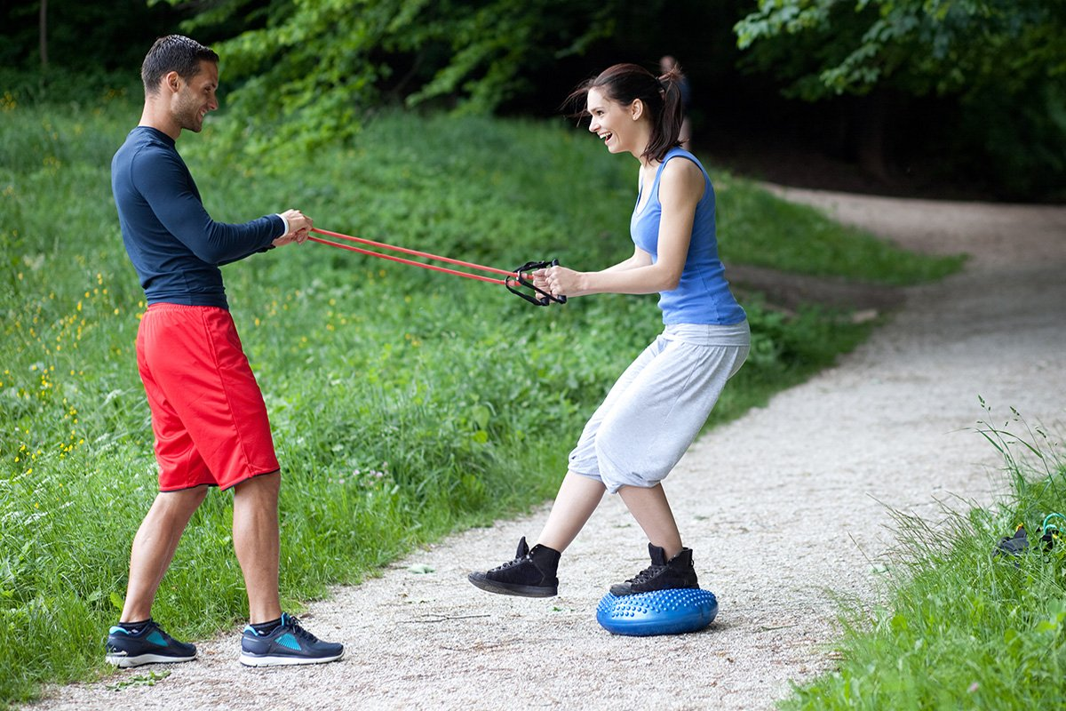 trainer and client resistance band exercises outdoors