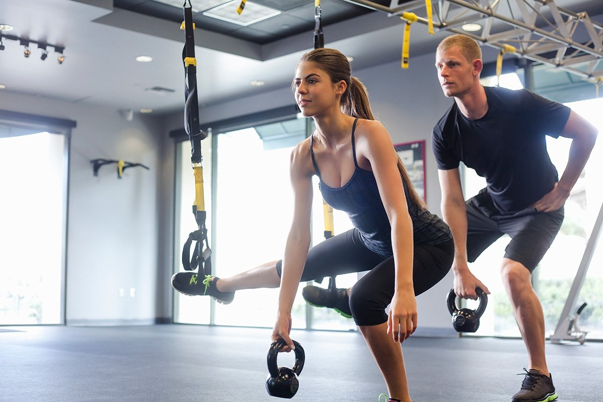 trainers doing kettlebell squats