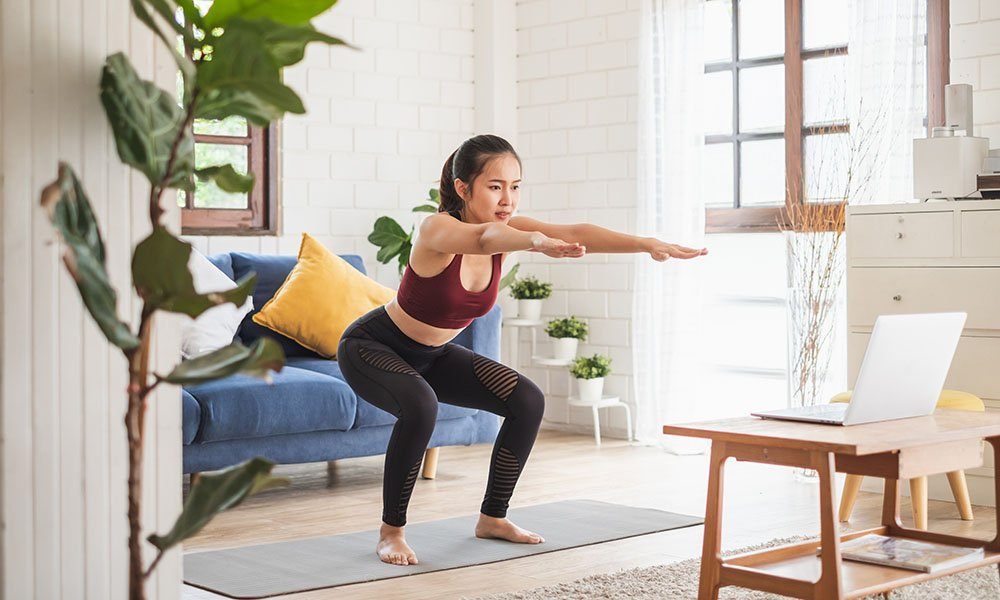 a woman doing a body weight squat in her home