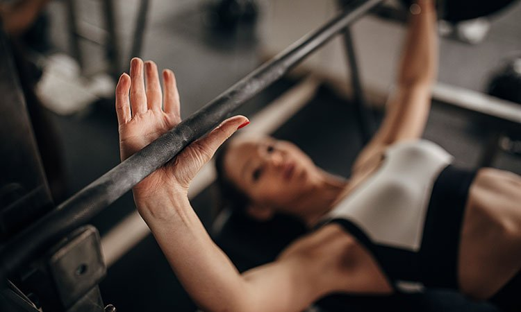 a woman bench pressing with neutral grip