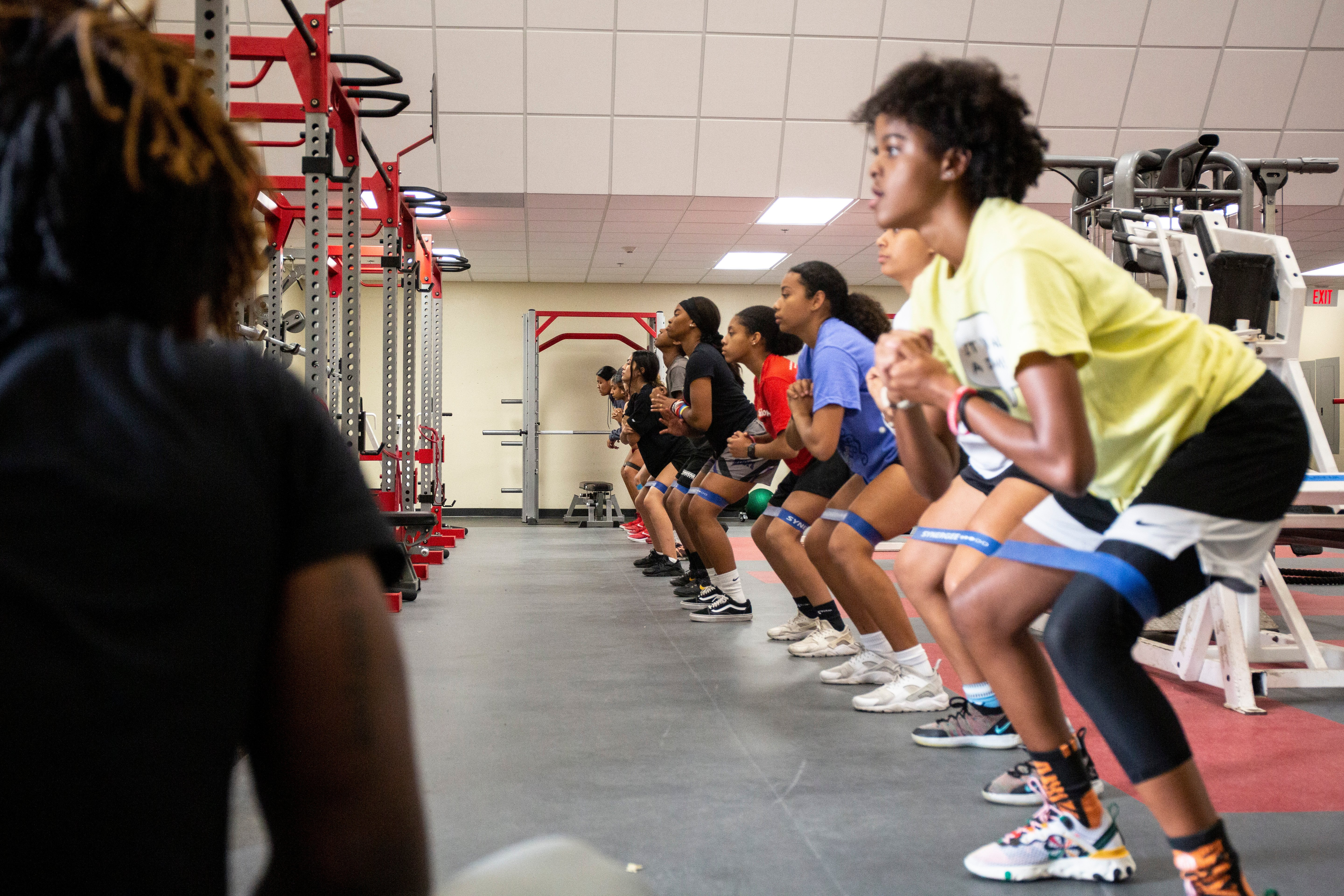 youth doing banded walks in a gym