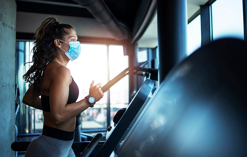 lady running on a treadmill with mask