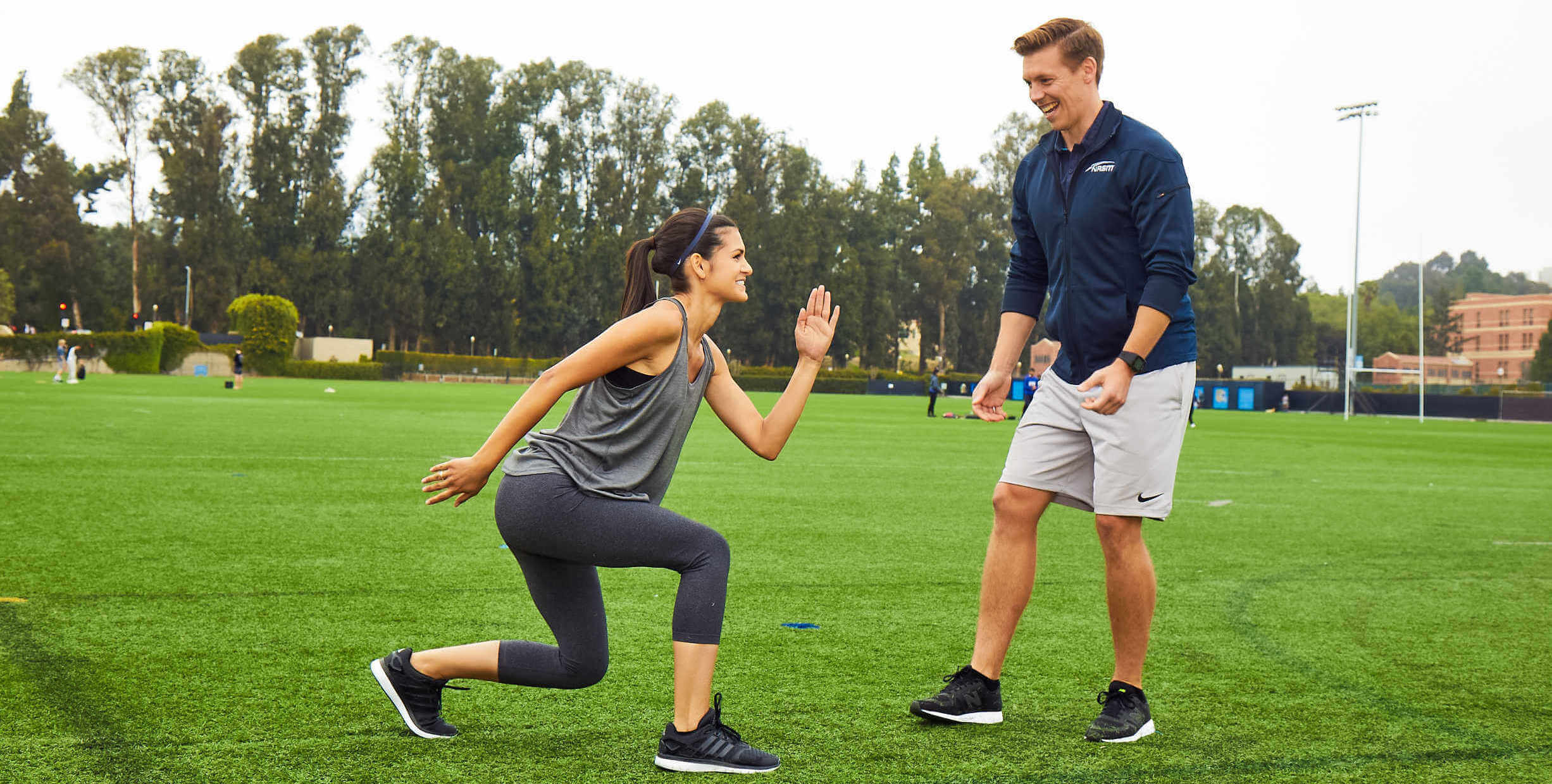 Personal trainer working with client outdoors