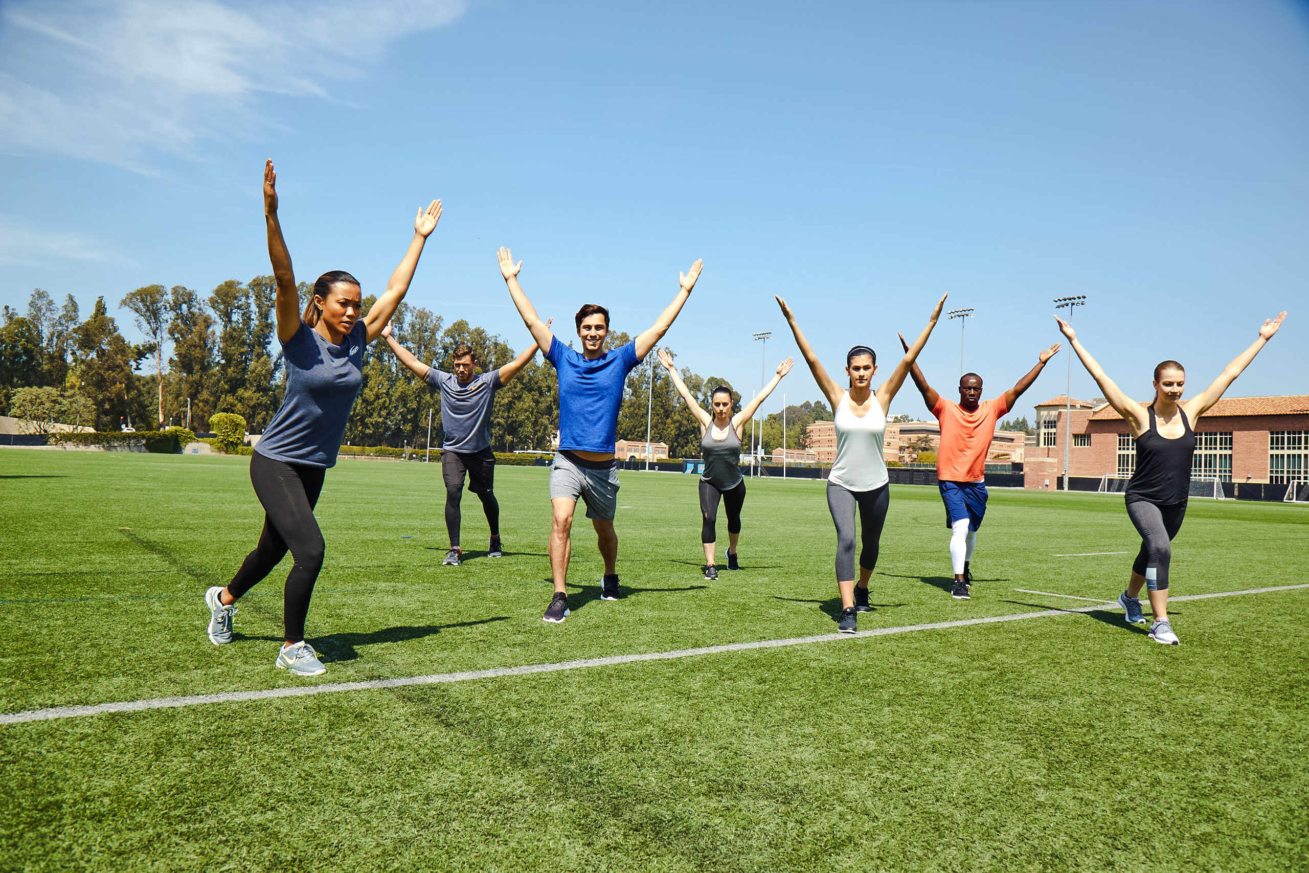 Group workout class doing exercise outdoors