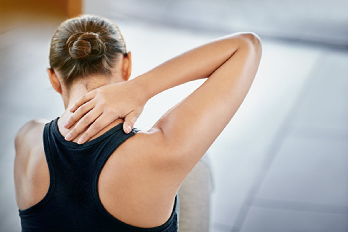 Woman with neck pain holding her sore muscles