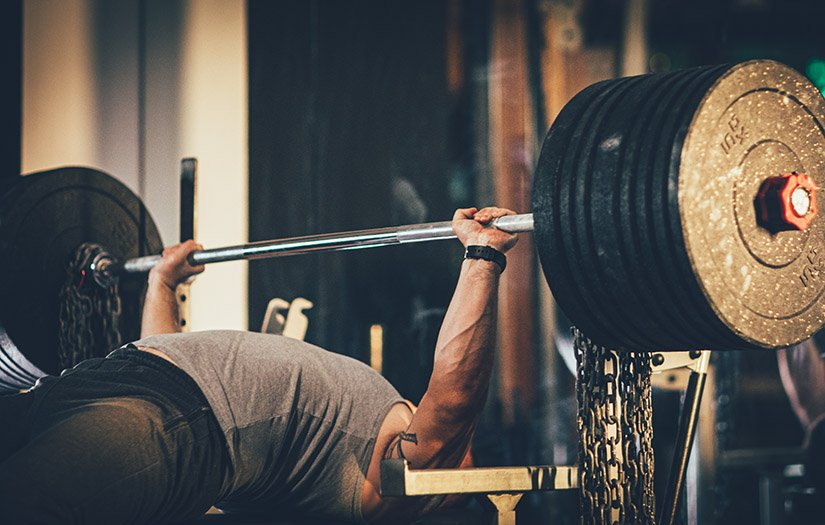 man bench pressing with chains