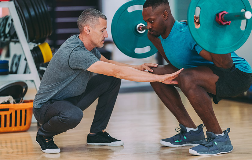 personal trainer teaching client how to squat properly