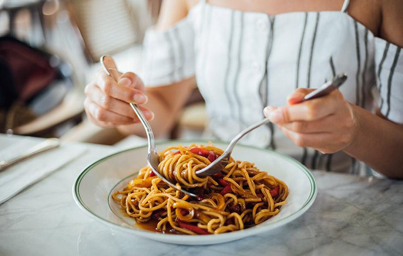 a woman eating carbs via spaghetti for weight loss