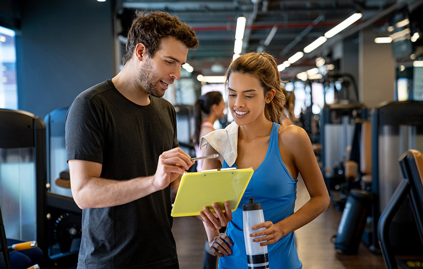 trainer with clipboard going over workout with client