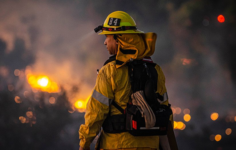 firefighter looking at a fire in the distance