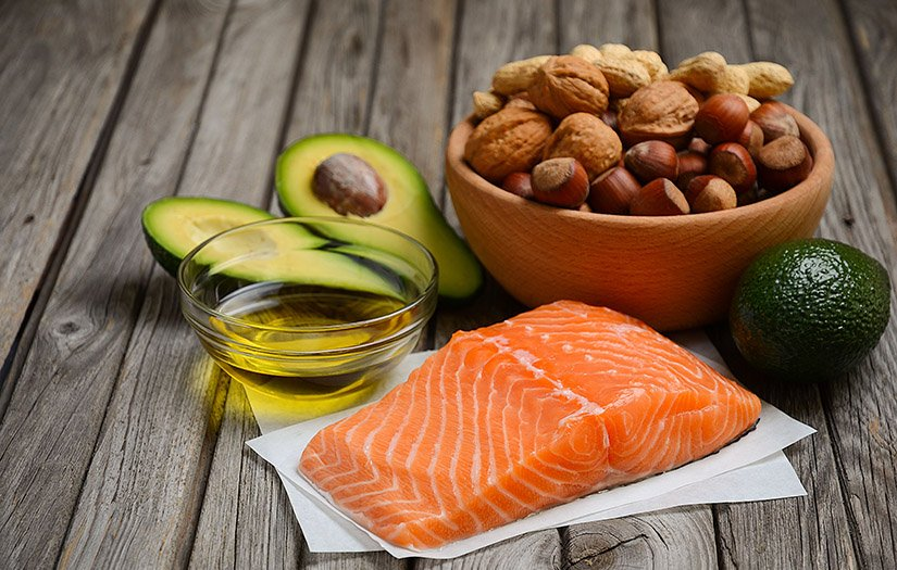 an assortment of healthy fats with olive oil, nuts, and avocado