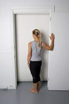 woman doing a standing chest stretch
