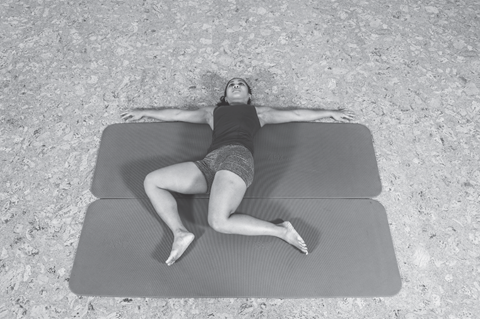 woman lying on back doing a dynamic stretch on mat