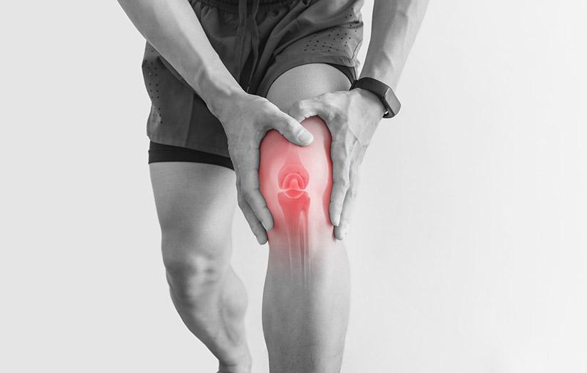man clutching his knee in pain