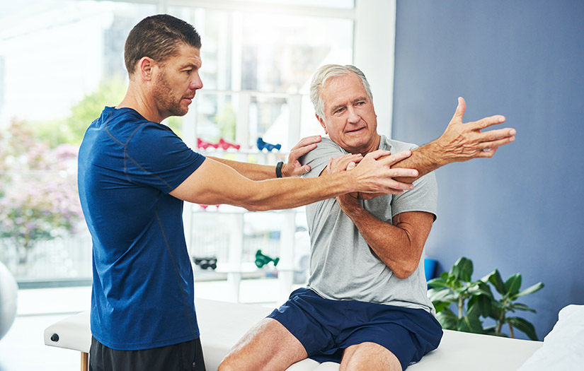 man measuring a client's joint range of motion