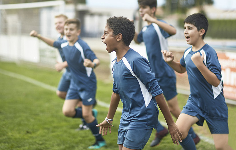 kid athletes celebrating on soccer field
