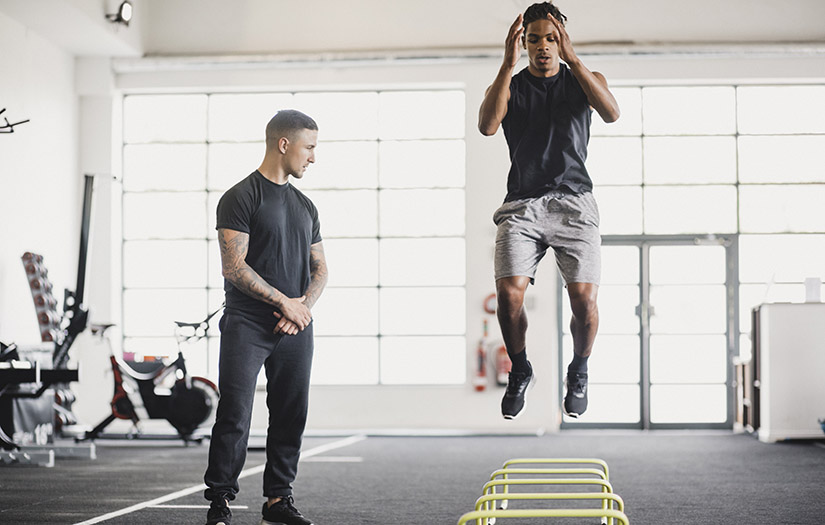 personal trainer training athlete with ladder drills