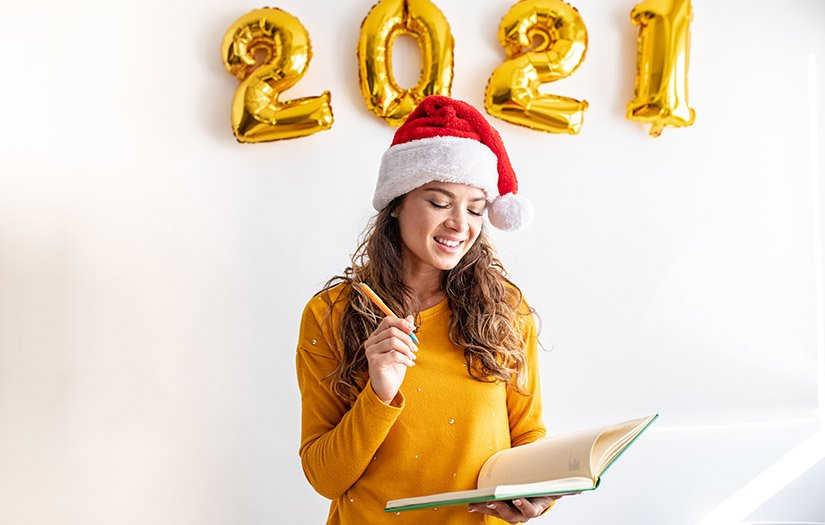 woman writing her new years resolutions for 2021