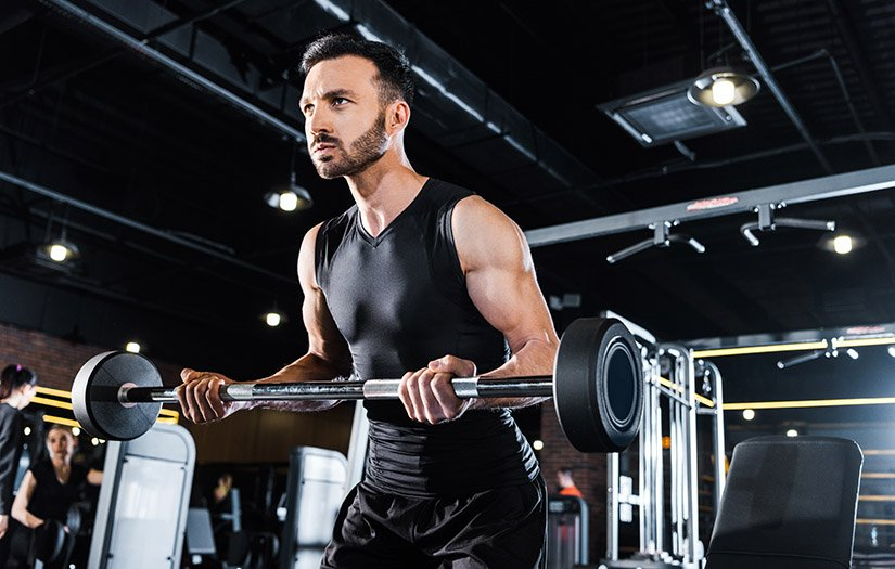 a man doing progressive overload workouts in the gym