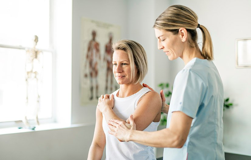 physiotherapist helping a woman's range of motion