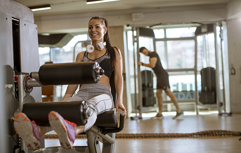 woman using a seated leg curl machine