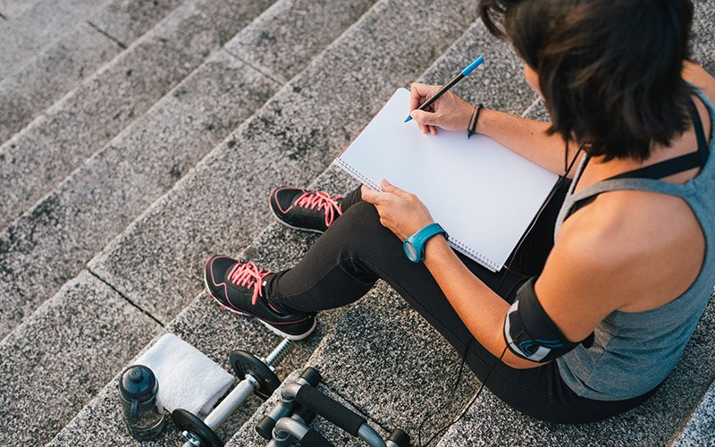 trainer setting smart fitness goals for herself with a notepad