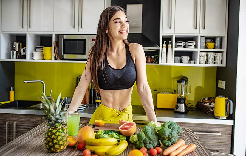 a vegan athlete standing in front of fruit on a kitchen table