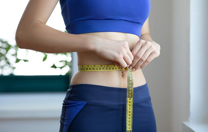 woman measuring her waist for weight loss