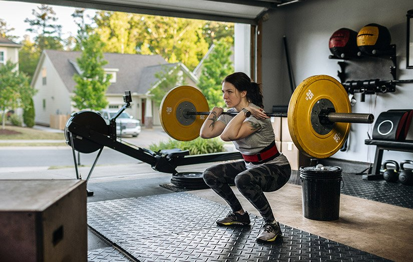 a woman doing a front squat in her garage gym