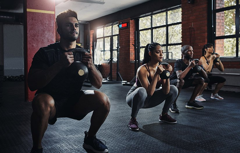 beginners doing kettlebell squats in a gym